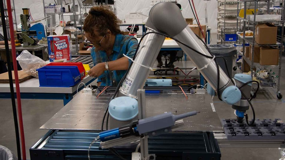 Woman on factory line works next to cobot