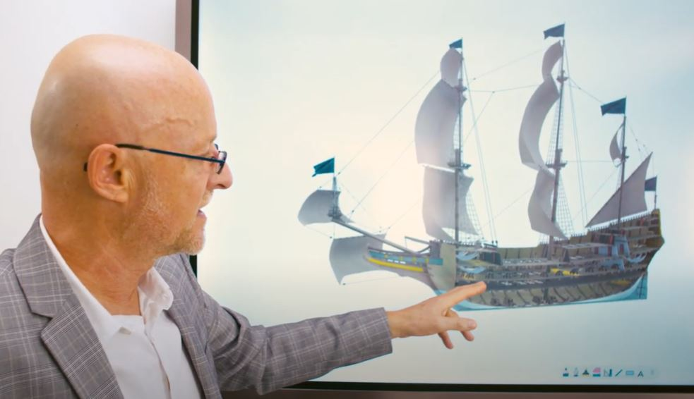 Man gestures at 3D model of ship