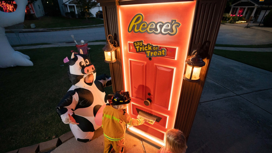 Trick or treaters receive candy from robotic Reese's door