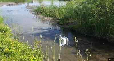 metal box on pole monitoring stream of water