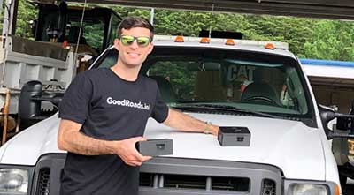 Man standing in front of truck with GoodRoads sensor box