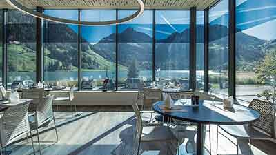 Smart glass enclosed dining room with lakeside view