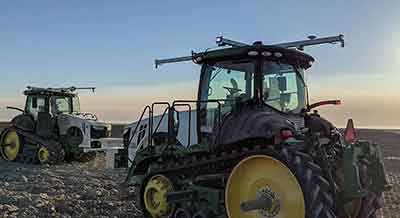 Two tractors outfitted with sensors and cameras in field