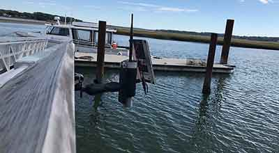 Flood sensor attached to boat dock with boat in background