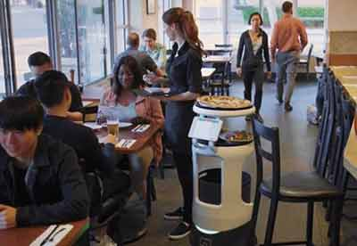 A robot with meal options joins a waitress getting orders at a guest's table
