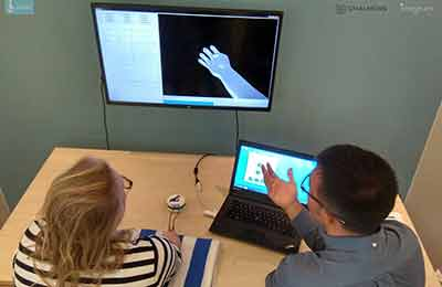 A man and woman look at screen with an image of a hand.