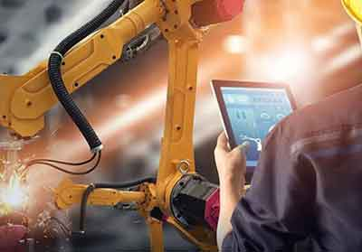 man looks at data on tablet with yellow mechanical robotic arm and sensors in background