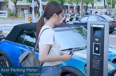 Woman looking at smart parking meter with cars parked behind her