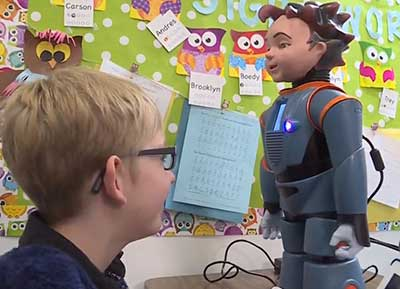Student looks at robot on desk for visual emotional clues