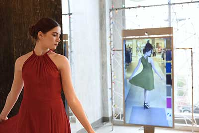Young woman in red dress sees smart mirror image of herself in green dress