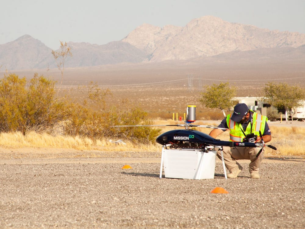 Man in yellow safety vest and hat inspecting drone