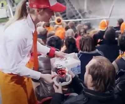 Female in apron, tie and hat delivers food to guests at arena