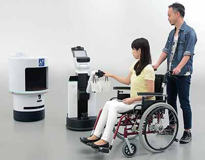 woman in wheelchair pushed by man interacts with robot