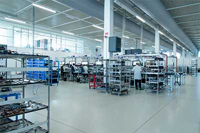 Four people in manufacturing room examining products