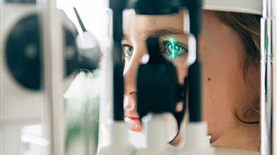 Medical instrument shines green light into female patient's eye