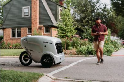 Man looking at phone while walking down a street passes grey delivery robot