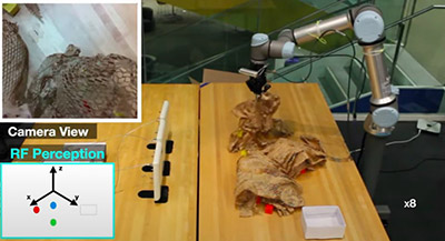 Robot arm examines material on table and screens show what it is seeing