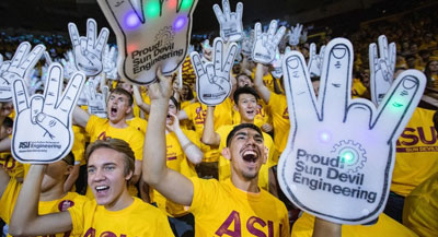 Fans with yellow shirts and large hands with IOT sensors cheer for team