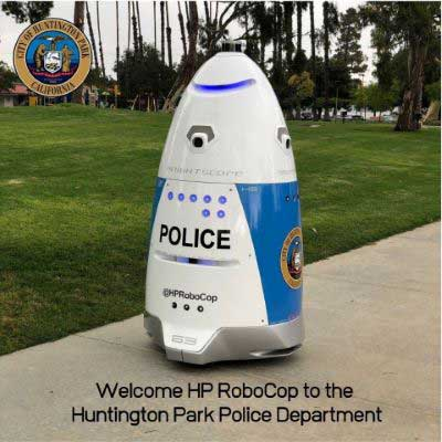 Blue and white police robot on sidewalk in park