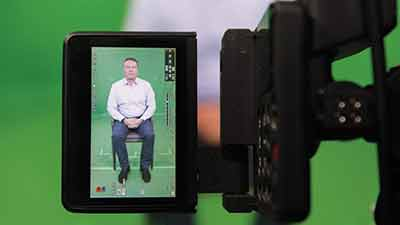 video screen image of man sitting in chair with green screen behind him